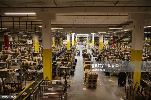 Workers monitor automated conveyor belt operations in the packaging room at Amazoncom Inc's new fulfillment center in Kolbaskowo Poland on Friday Feb...