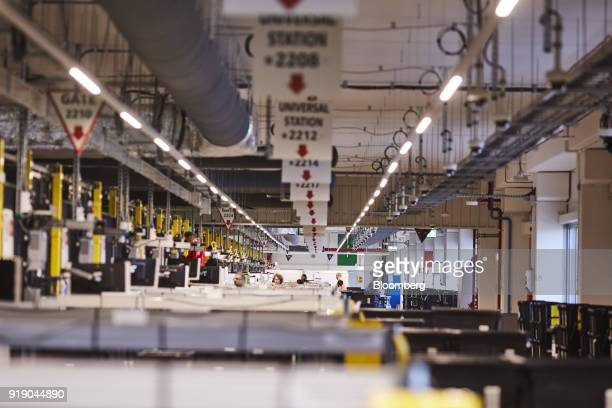Workers monitor automated conveyor belt operations in the robotics field unit Amazoncom Inc's new fulfillment center in Kolbaskowo Poland on Friday...