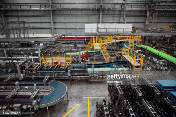 Workers monitor bottles of CocaCola Co brand water moving along a conveyor at the CocaCola Cambodia Bottling Plant operated by Cambodia Beverage Co...