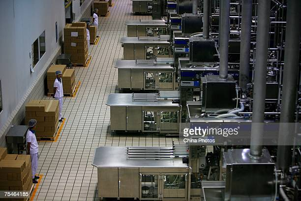 Workers monitor liquid milk product lines at a plant of Yili Industrial Group Company on July 18 2007 in Huhehot of Inner Mongolia Autonomous Region...