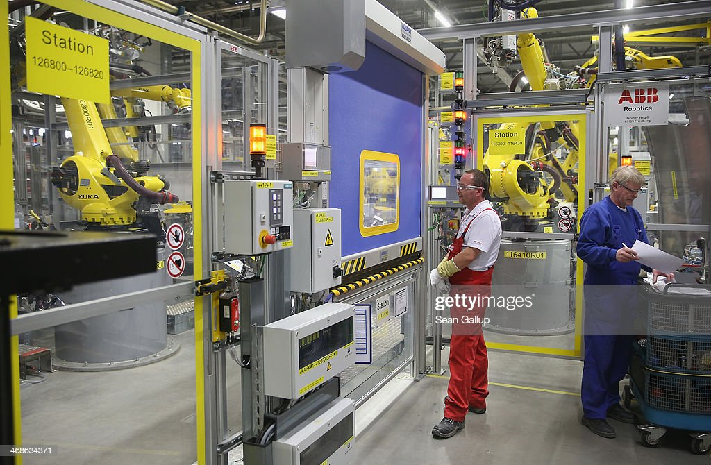Workers monitor robots welding the bodies of Porsche Macan SUVs at the heavily automated Porsche Macan factory at the Porsche plant on February 11, 2014 in Leipzig, Germany. Porsche plans to produce 50,000 of the new small SUV Macan annually.