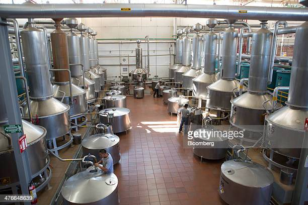 Workers monitor the distilling process for Don Julio Blanco brand tequila at Tequila Don Julio SA de CV's La Primavera distillery in Atotonilco in...