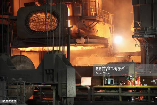 Workers monitor the operation as steel is melted at 3000 degrees Fahrenheit in an electric arc furnace at the NLMK Indiana steel mill on March 15...