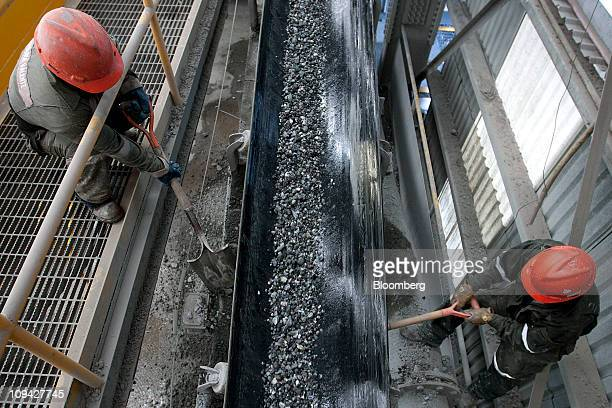 Workers monitor unprocessed silver as it moves alone a conveyor belt at the Fresnillo Plc silver mine in Zacatecas Mexico on Wednesday Feb 23 2011...