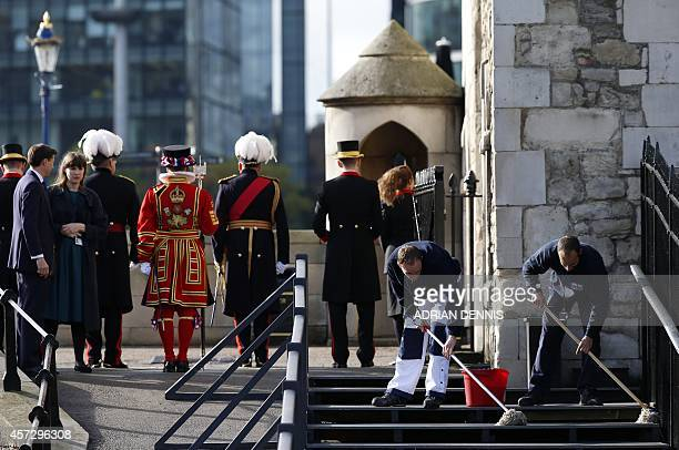 Workers mop the stairs ahead of a visit by Britain's Queen Elizabeth II and her husband Prince Philip to the Tower of London's 'Blood Swept Lands and...
