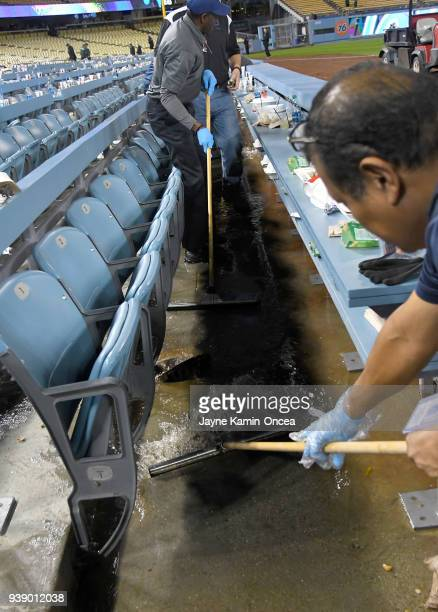 Workers mop up water from a sewer line break causing the spring training game between the Los Angeles Angels of Anaheim and the Los Angeles Dodgers...