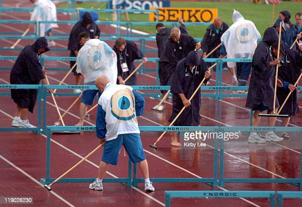 Workers mop water from the track during rain delay in the IAAF World Championships in Athletics at Olympic Stadium in Helsinki Finland on Tuesday...