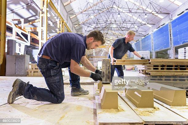 Workers moulding stone in architectural stone factory