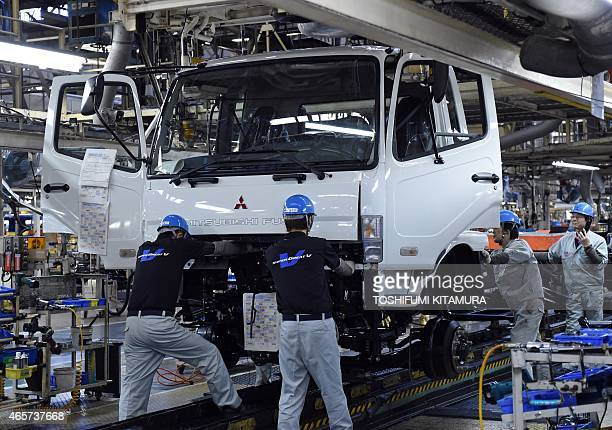 Workers mount a cabin onto a chassis on the line of the Mitsubishi Fuso Truck and Bus Corporation Kawasaki plant in Kawasaki on March 10 2015 The...