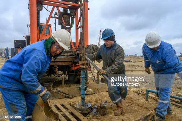 Workers mount a pump jack at Bibi Heybat Oil Field situated at the coast of the Caspian Sea outside Baku on March 19 2019 Bibi Heybat's first oil...