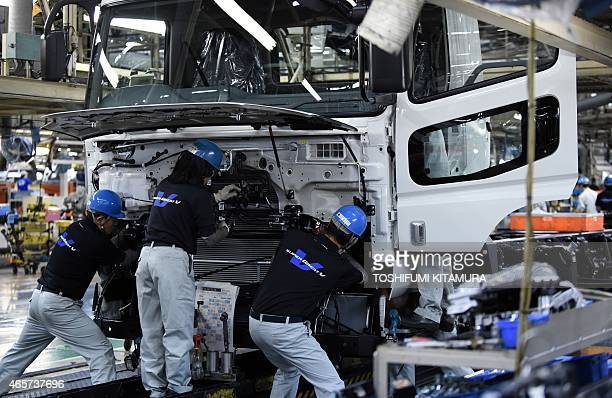 Workers mount the cabin onto the chassis on the assemble line of the Mitsubishi Fuso Truck and Bus Corporation Kawasaki plant in Kawasaki on March 10...