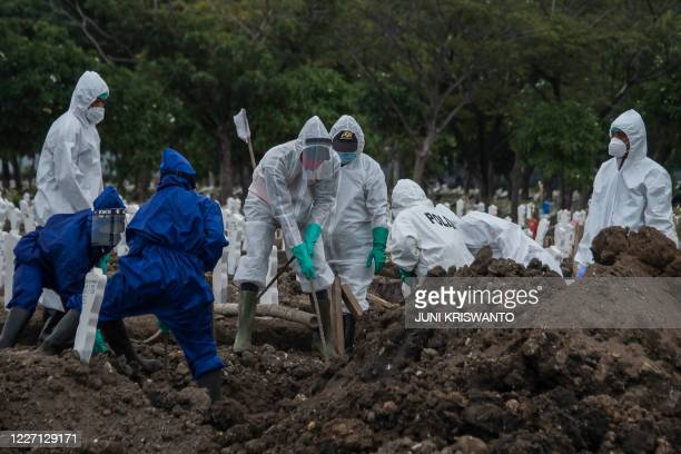 Workers move a coffin to a burial site for victims of the COVID-19 coronavirus at Keputih cemetery in Surabaya, East Java on July 15, 2020.