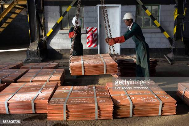Workers move batches of copper sheets, which are stored in a warehouse and wait to be loaded on trucks on July 6, 2016 in Mufulira, Zambia. The...