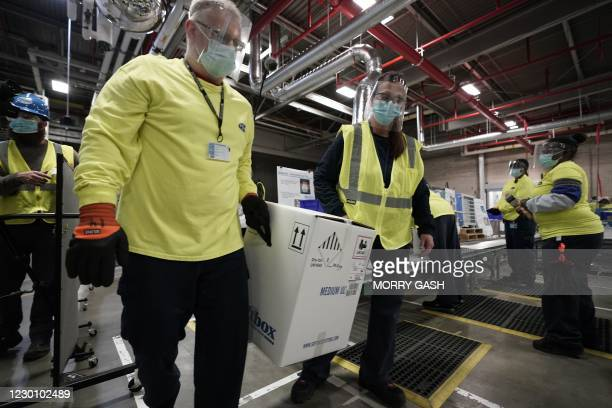 Workers move boxes containing the Pfizer-BioNTech Covid-19 vaccine as they are prepared to be shipped at the Pfizer Global Supply Kalamazoo...