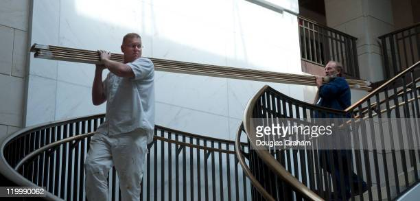 AOC workers move crown molding into the basement of the Capitol Visitors Center via a spiral staircase on July 28 2011