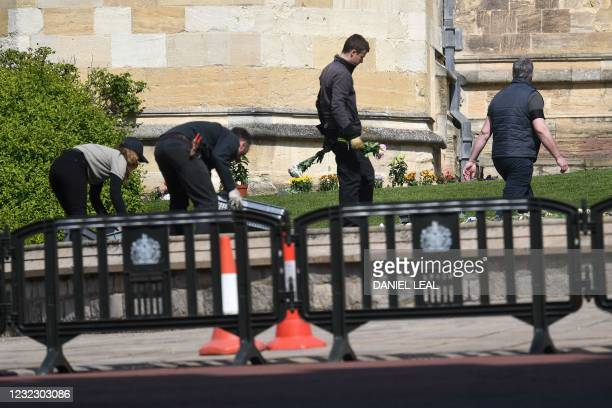 Workers move flowers left as tributes to inside the grounds of Windsor Castle in Windsor, west of London, on April 14 following the April 9 death of...