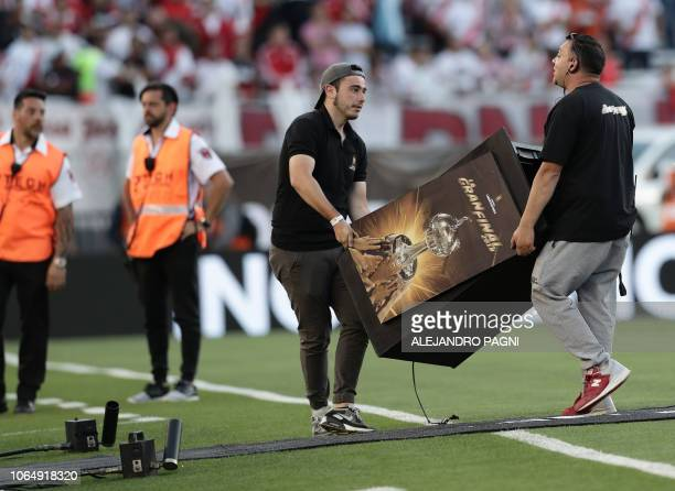 Workers move furniture from the field at the Monumental stadium in Buenos Aires as authorities decide if the allArgentine Copa Libertadores second...