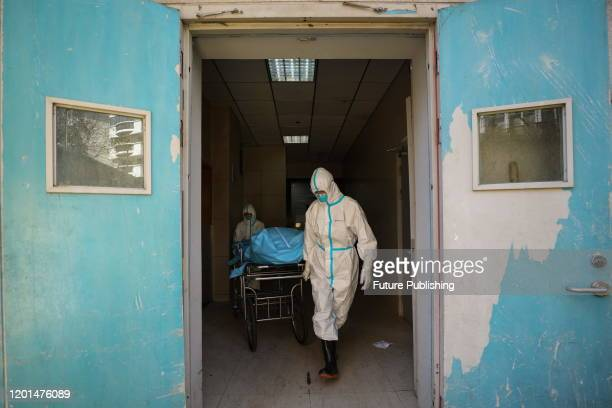 Workers move out the body of a COVID-19 victim in a hospital in Wuhan in central China's Hubei province Sunday, Feb. 16, 2020.- PHOTOGRAPH BY Feature...