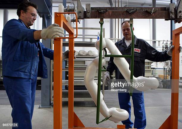 Workers move parts of a gas-insulated switchgear at the ABB high-voltage products plant in Hanau, Germany, on Tuesday, Nov. 6, 2007. ABB Ltd. Is the...