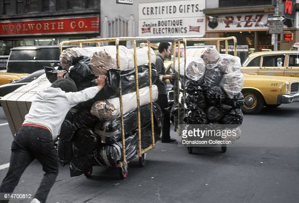Workers move rolls of fabric across 8th Avenue in the Garmant District in1976 in New York City New York