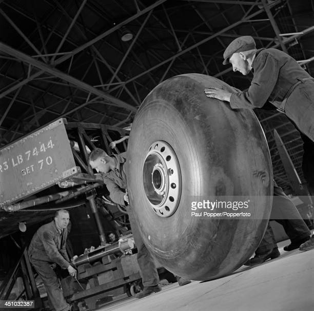 Workers move the wheel of an Avro Lancaster heavy bomber into position on the production line at an Avro factory in Greater Manchester 16th March...