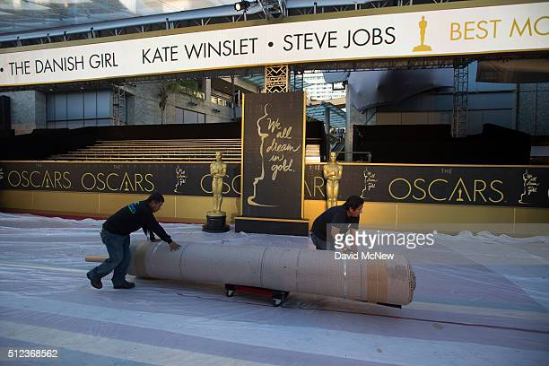 Workers moves rolls of carpet in the red carpet arrivals area on Hollywood Boulevard as preparations continue for the 88th Annual Academy Awards at...