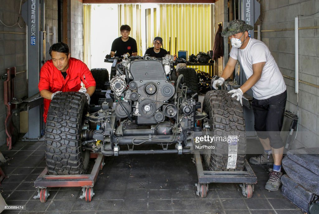 """Workers moving to re imstalled lower body at mohenic garages in Paju, South Korea. A 20-year-old beat up Hyundai SUV isn't anyone's idea of a dream car. But used Hyundai Gallopers, priced between $2,000 to $3,000 at second-hand car markets, are making a comeback , reborn as upwards $80,000 luxury vehicles at the hand of former furniture designer Henie Kim. Kim is now the CEO of Mohenic Garages, a car rebuilding company based in Paju has transformed the boxy classic into one of South Korea's most highly-desired cars. """"As a former designer, I wanted make everything perfect."""" The remade """"Mohenic G"""", as they're known, take their design cues from the 1990s and come in a variety of custom colors from """"mint racing green"""" to """"midnight cerulean blue"""". Demand for the """"Mohenic G"""" has steadily risen, and the waitlist is long. Since 2013, only 43 cars have been rebuilt and 48 customers are on a waiting list. Production is slow though since the company expanded, they're able to produce 30 cars a year, or about 2 cars a month. A team of two dozen workers transform each car in a meticulous process that includes prying the car cabin from its frame, sanding, removing corrosive substances, polishing and painting."""
