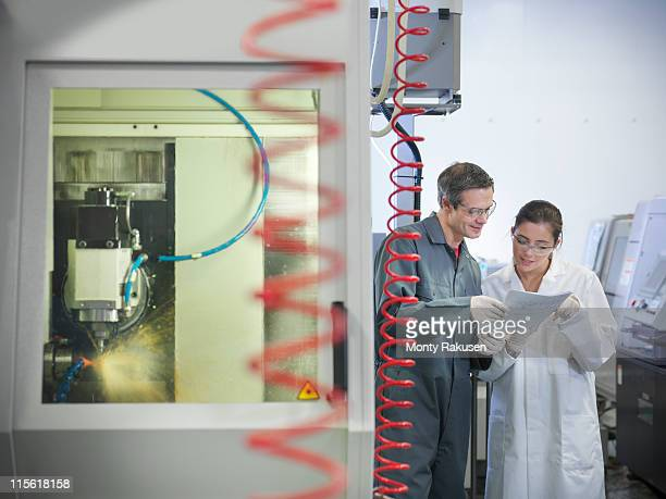 workers next to computerised lathe - white jumpsuit stock pictures, royalty-free photos & images