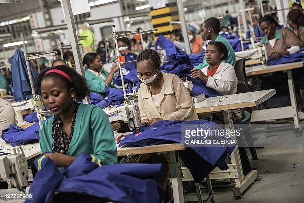 Workers of a foreign-owned textile factory sew on machines during their shift on September 1, 2015 in the factory on the outskirts of Matsapha,...