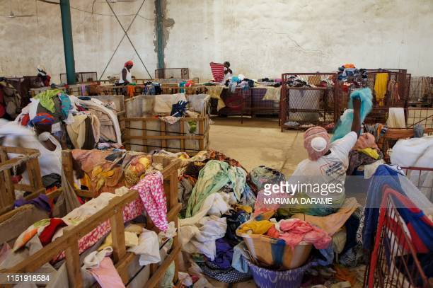 Workers of a recycling centre of secondhand textile of the French social enterprise Le Relais sort through bales of clothes in Diamniadio Senegal on...