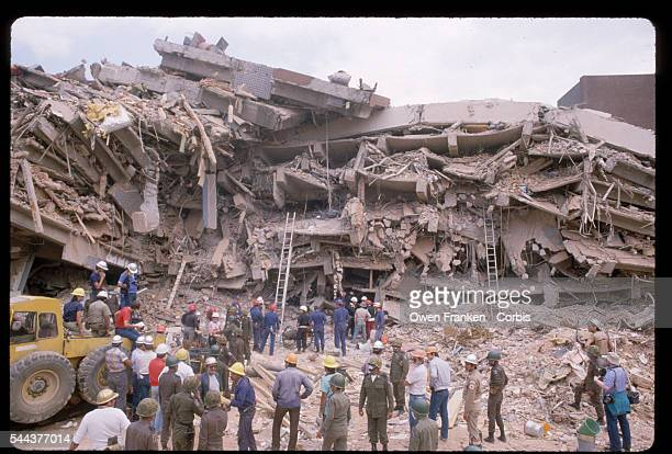 Workers of a rescue operation stand before a building completely demolished in a the 1985 earthquake in Mexico City Mexico