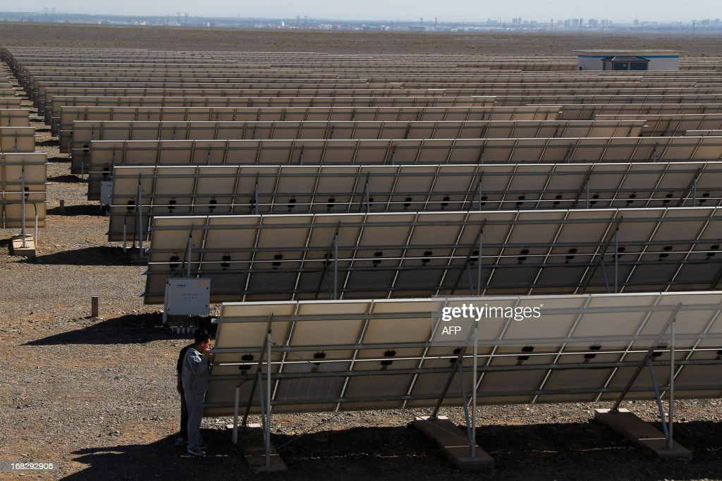Workers of a solar power plant check their solar panels in Hami, northwest China's Xinjiang Uygur Autonomous Region on May 8, 2013. The EU executive on May 8 proposed heavy anti-dumping tariffs of around 47 percent on imports of Chinese solar panels, a European Union source said. CHINA