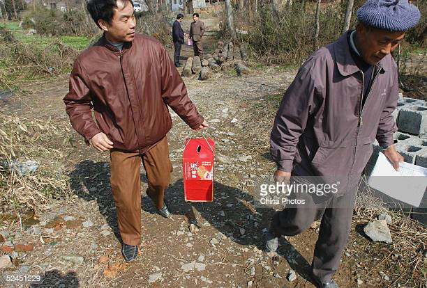 Workers of an mobile polling station of Fengxing Village carry the ballot box and registration forms to a villager's home on March 18 2005 in...
