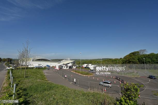 Workers of Britain's NHS arrive by car to be tested for the novel coronavirus COVID-19, at the entrance to a testing centre set up at the American...