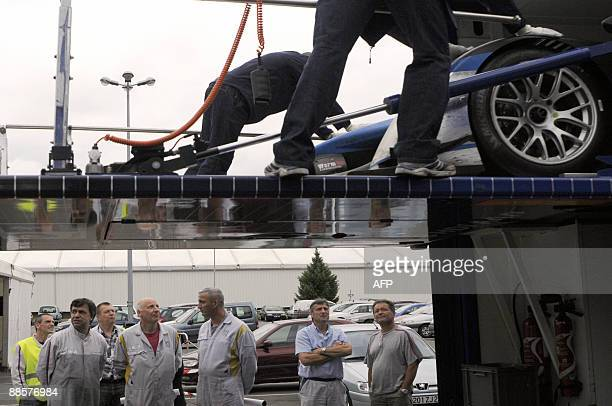 Workers of French car maker group look at the Peugeot 908 HDiFAP car which won the Le Mans 24 hours race as its being unloaded prior to its...