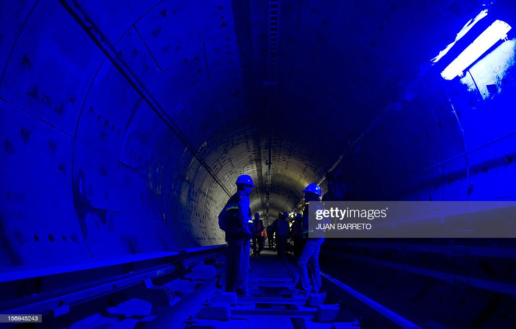 Workers of French company Alstom walk in a tunnel during the visit of French Junior Minister for the Social Economy, Benoit Hamon (not in frame) in Caracas on November 25, 2012. Venezuela and France signed seven cooperation agreements in areas such as manufacturing, mining, science and tourism during Hamon's visit to Caracas.