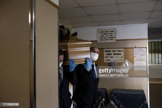Workers of funeral home company Palmero carry the coffin of a victim of COVID19 on April 24 2020 at the morgue of the Saluzzo hospital near Cuneo...