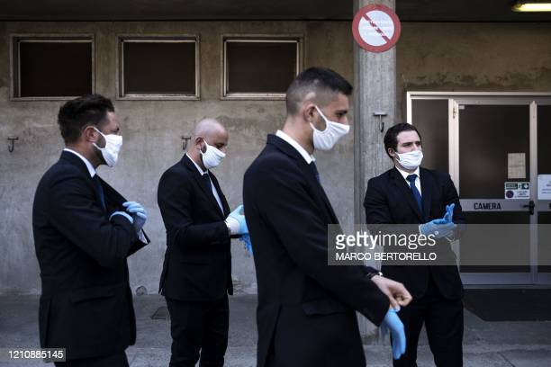 TOPSHOT Workers of funeral home company Palmero put on protective gloves on April 24 2020 at the morgue of the Saluzzo hospital near Cuneo...