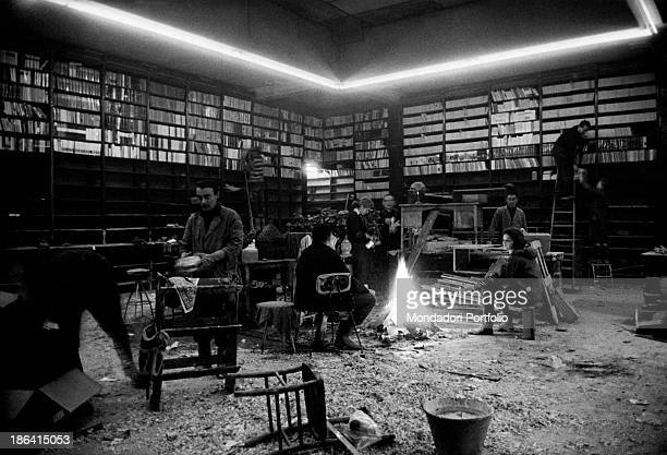 Workers of Marzocco library damaged by the flood of the Arno River warming up around the fire Florence November 1966
