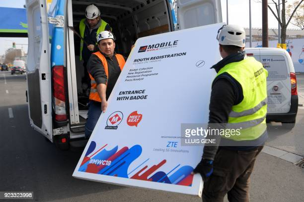 Workers of Mobile World Congress carry a billboard at the venue's entrance on February 23 ahead of the start of the world's biggest mobile fair held...