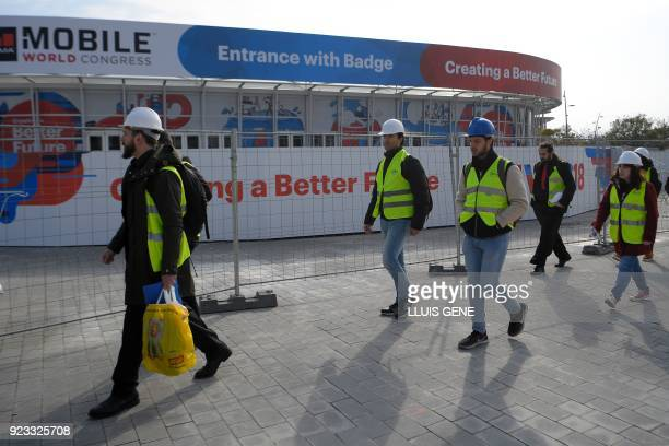 Workers of Mobile World Congress go through the venue's entrance on February 23 ahead of the start of the world's biggest mobile fair held from...