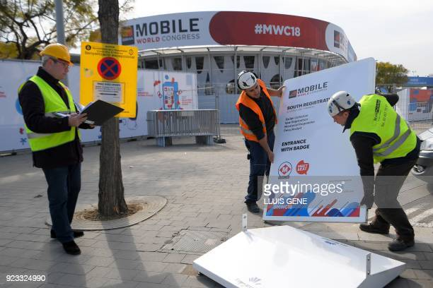 Workers of Mobile World Congress set up a billboard at the venue's entrance on February 23 ahead of the start of the world's biggest mobile fair held...