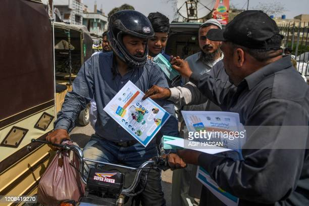 Workers of ruling Pakistan Tehreek-e-Insaf political party, distribute facemasks and pamphlets about basic protective measures against the COVID-19...