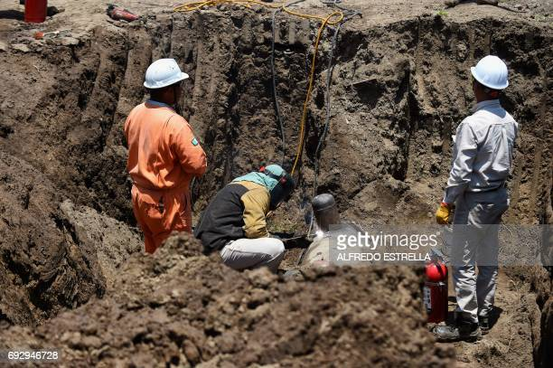 Workers of stateowned oil giant PEMEX repair a leak in a clandestine fuel siphoning area in Tepeaca Puebla State Mexico on May 26 2017 Violent...
