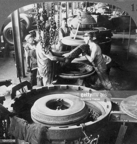Workers of the automobile industry stripping a tire from its mould in a factory of Akron, Ohio around 1920-1930. This process consists in heating the...