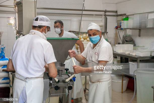 Workers of the Capricci di Latte dairy knot the pasta by hand to create the Apulian mozzarella on May 22, 2020 in Polignano, Italy. Restaurants,...