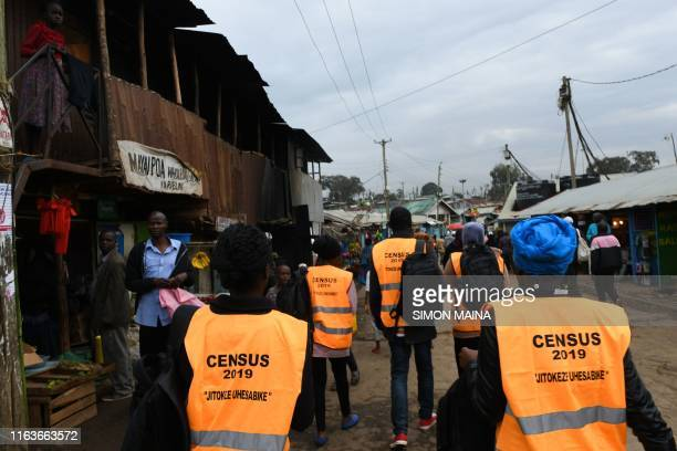 Workers of the Census enumeration walk past vendors selling wares August 24 2019 in Kibera's district in Nairobi before the begining of the...