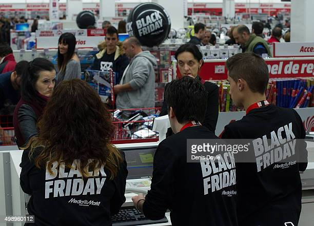 Workers of the consumer electronics company Media Markt wear Black Friday shirts while attending customers during 'Black Friday' discounts on...