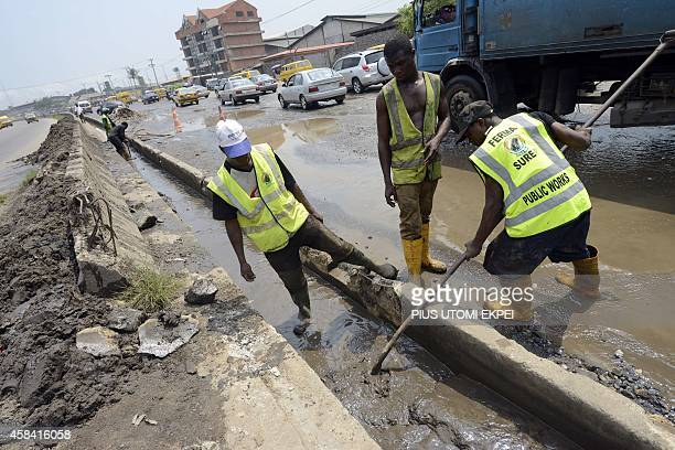 Workers of the Federal Roads Maintenance Agency tries to clear the gutter on Apapa Oshodi expressway that leads to Apapa ports West Africa's busiest...