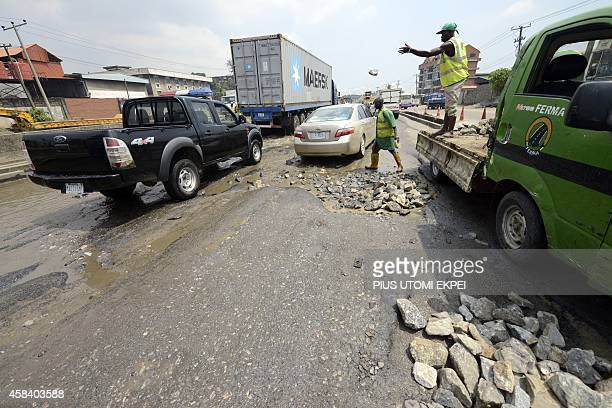 Workers of the Federal Roads Maintenance Agency try to fill with stones waterlogged potholes on Apapa Oshodi expressway that leads to Apapa ports...
